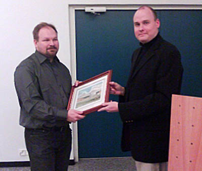 Tuomas Kuosmanen (left) receives the first prize of FoMA's photo competition.